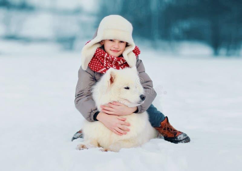 Dziecko ściska białego Samoyed psa w zima dniu fotografia royalty free