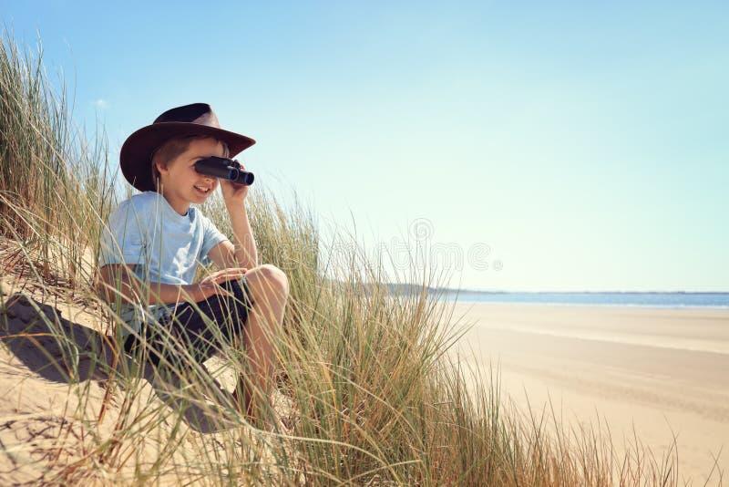 Dziecko badacz z lornetkami przy plażą fotografia royalty free