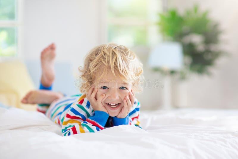 Dziecko bawić się w łóżku żartuje pokój Chłopiec w domu obraz royalty free