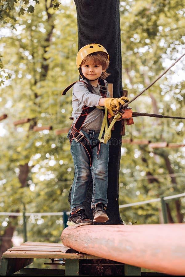 Dziecko bawiące się na placu zabaw Wędrówka w parku linowym w bezpiecznym sprzęcie Dziecko-klinicysta w trakcie szkolenia Chłopie obraz royalty free