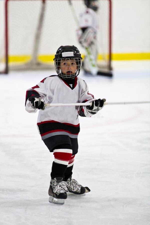 Dziecko bawić się mniejszościowego hokeja w arenie obraz royalty free