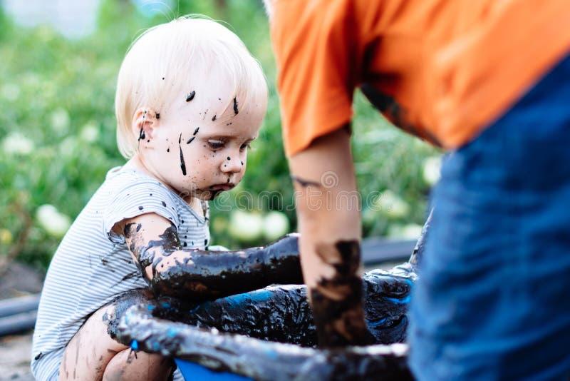 Dziecko bawić się w błocie na ulicie zdjęcie royalty free