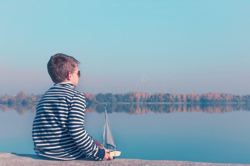 Dziecko bawić się z żeglowanie łodzią w pięknym świetle fotografia stock