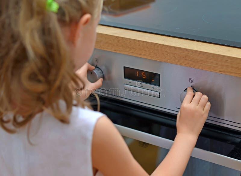 Dziecko bawić się z elektrycznym piekarnikiem zdjęcie royalty free