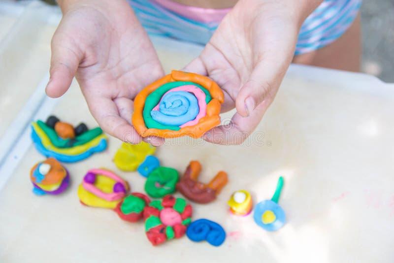 Dziecko bawić się z kolorowymi glinianymi robi zwierzę postaciami Zbliżenie na rękach obraz royalty free