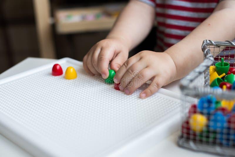 Dziecko bawić się z kolorowymi zabawkami siedzi przy okno mały chłopiec obraz royalty free