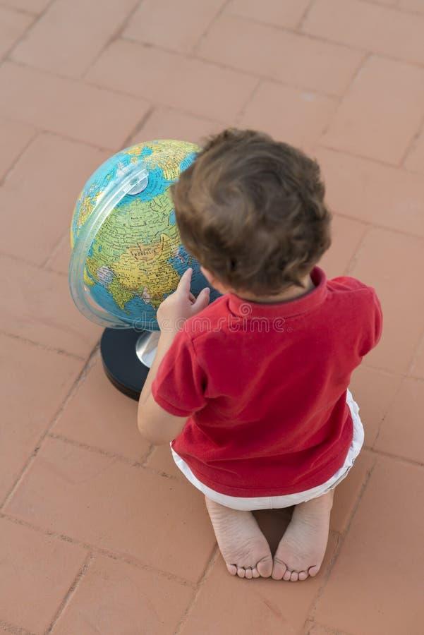 Dziecko bawić się z kulą ziemską obrazy royalty free
