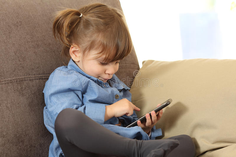 Dziecko bawić się z mądrze telefonem w domu fotografia royalty free