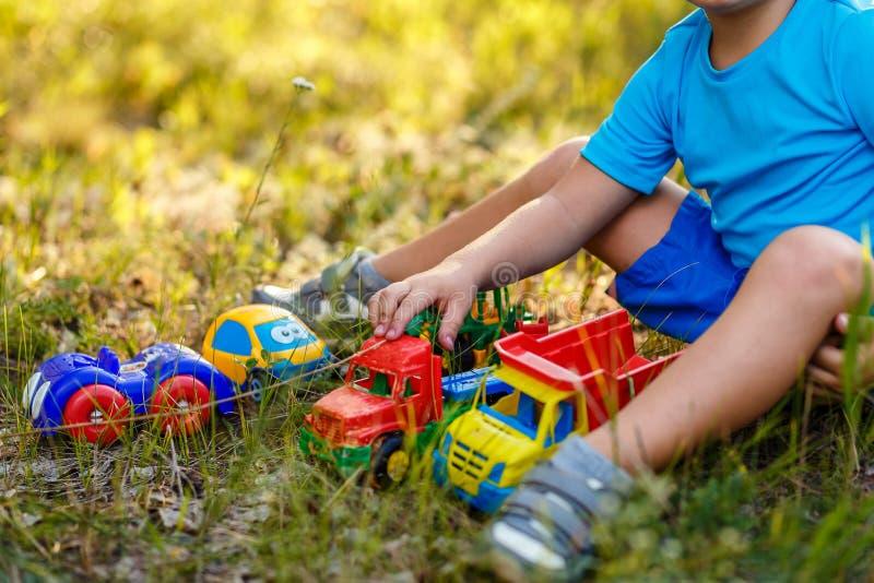 Dziecko bawić się z plastikowymi maszynami na trawie obrazy stock