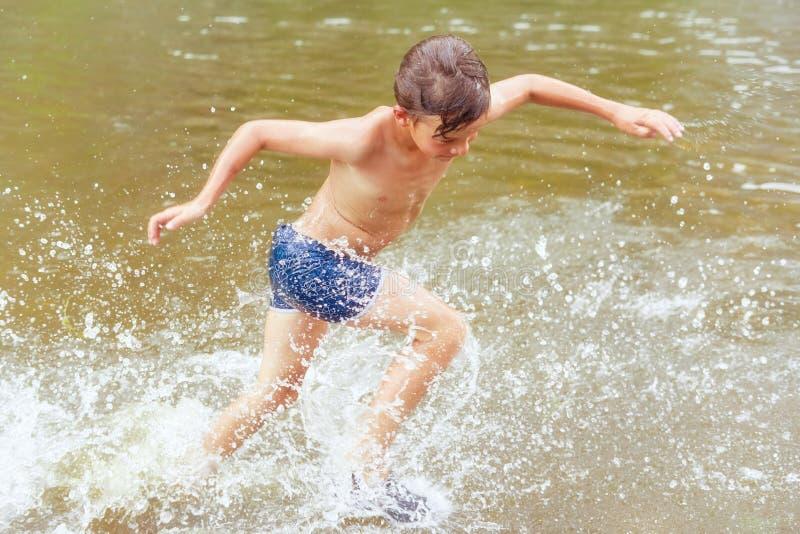 Dziecko biega w wodę Ruch radość i pluśnięcia tonowanie zdjęcie stock