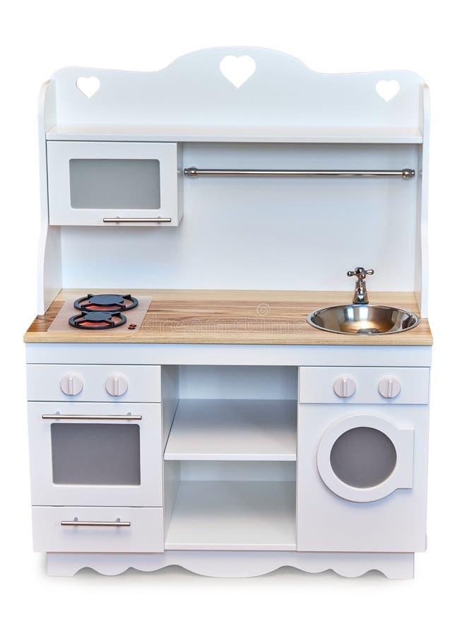 Dziecko biel barwił i drewniana zabawkarska kuchnia ustawia odosobnionego na białym tle zdjęcie royalty free