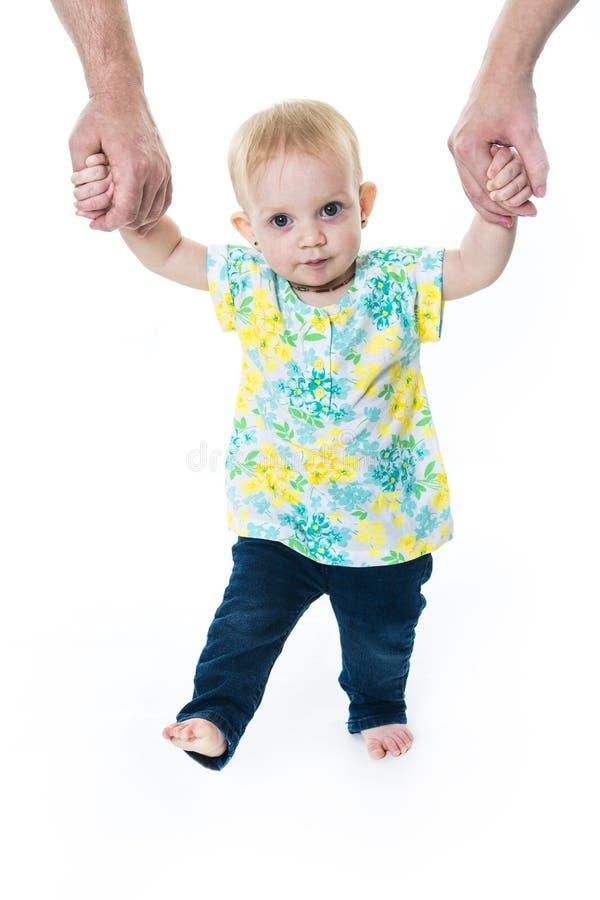 Dziecko bierze pierwszych kroki z macierzystą ojciec pomocą na białym tle obraz royalty free