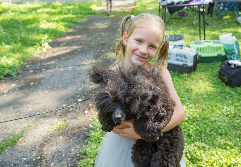 Dziecko blond dziewczyna czule obejmuje jego zwierzę domowe pudla psa przyja?? zdjęcia royalty free