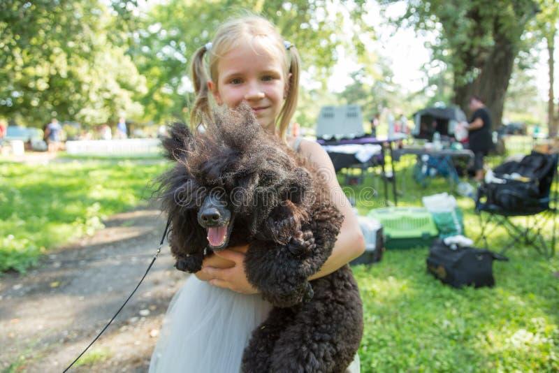 Dziecko blond dziewczyna czule obejmuje jego zwierzę domowe pudla psa przyja?? zdjęcie stock
