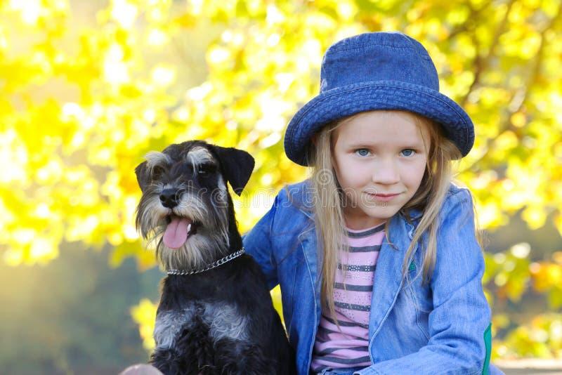 Dziecko blond dziewczyna czule obejmuje jego zwierzęcia domowego schnauzer psa przyja?? Jesie? kolory zdjęcia royalty free