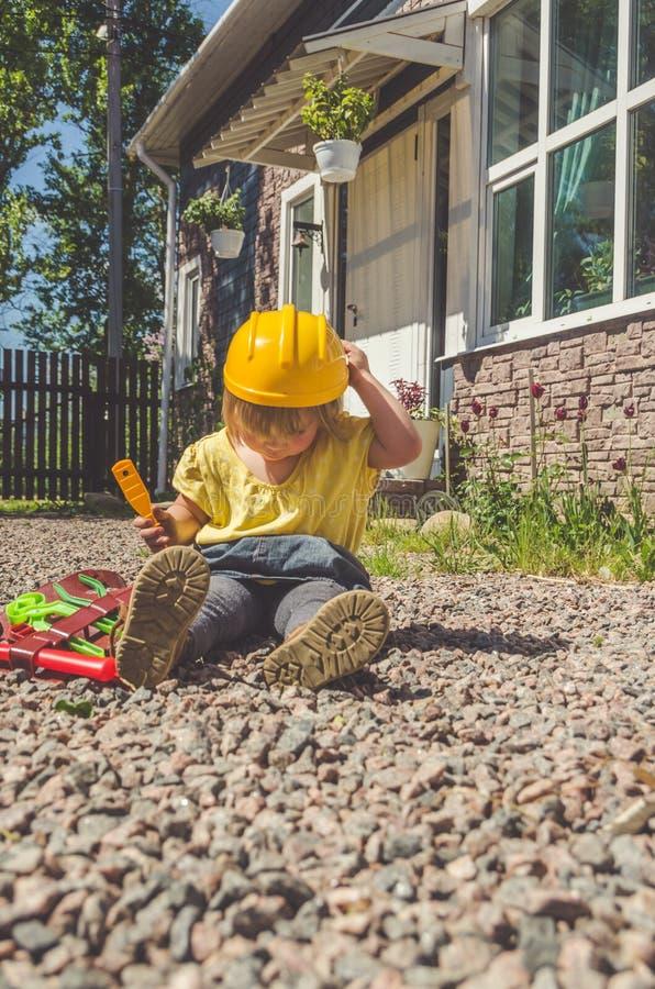 Dziecko budowniczy z hełmem i set zabawki narzędzie obrazy royalty free