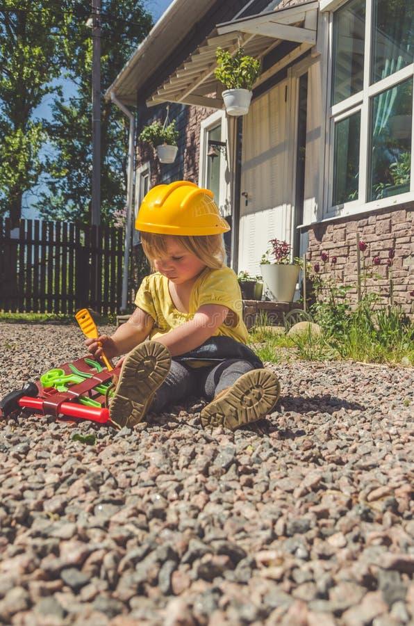 Dziecko budowniczy z hełmem i set zabawki narzędzie fotografia stock