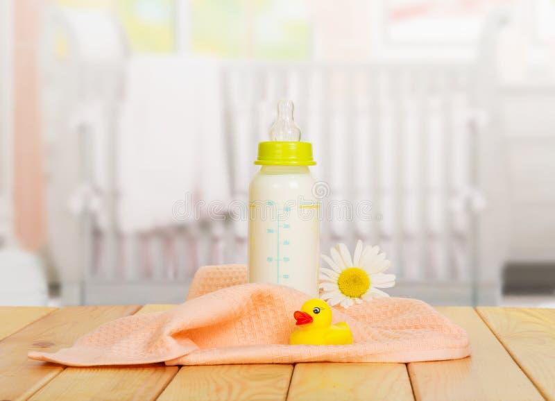 Dziecko butelki mleko, ręcznik i gumowa kaczka na tło kuchni, zdjęcie royalty free