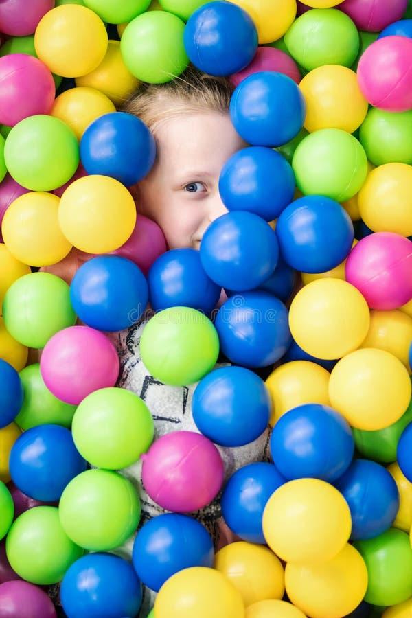 Dziecko całkowicie chował w kolorowych piłkach obrazy stock