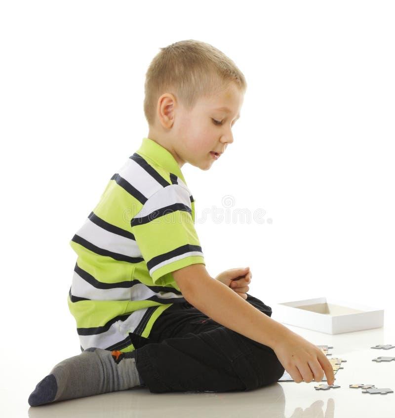 Dziecko chłopiec bawić się łamigłówkę odizolowywającą obrazy royalty free