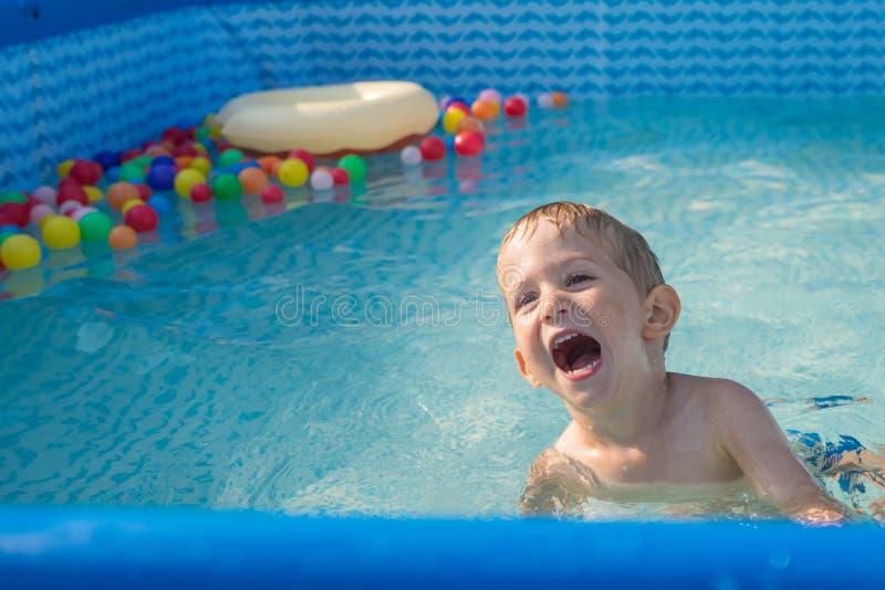 Dziecko chłopiec bawić się w małym dziecko basenie dziecka pluśnięcie i pływanie Szczęśliwa chłopiec bawić się z wodą bawi się na fotografia royalty free