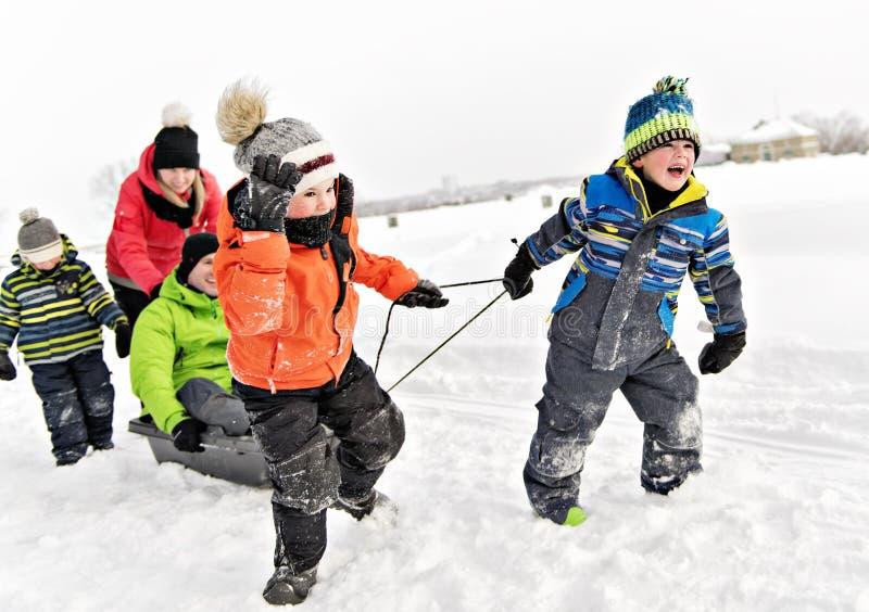 Dziecko chłopiec ciągnięcia saneczki Przez Śnieżnego krajobrazu obrazy royalty free
