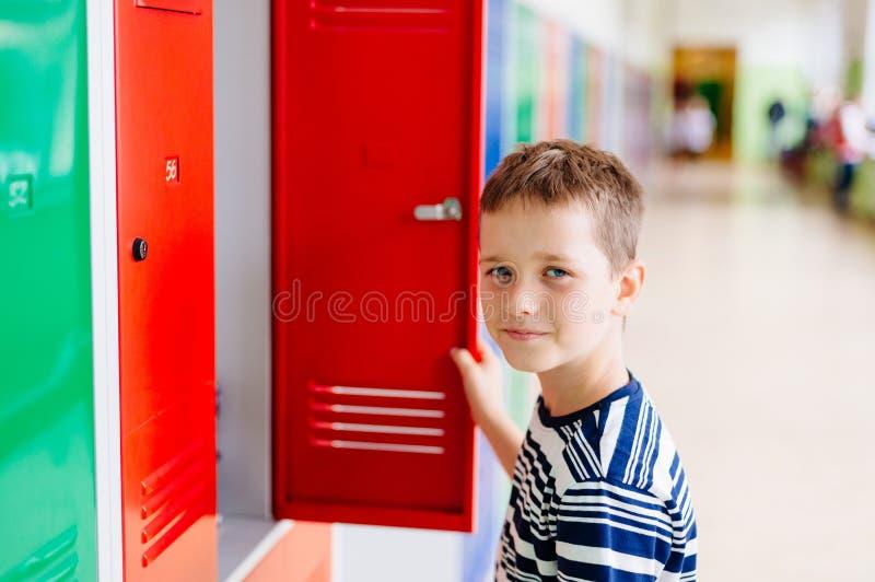 Dziecko chłopiec ciągnie out odziewa od metal szkoły szafki zdjęcie royalty free