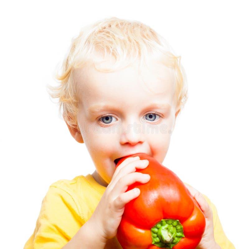 Dziecko chłopiec je słodkiego pieprzu obraz royalty free