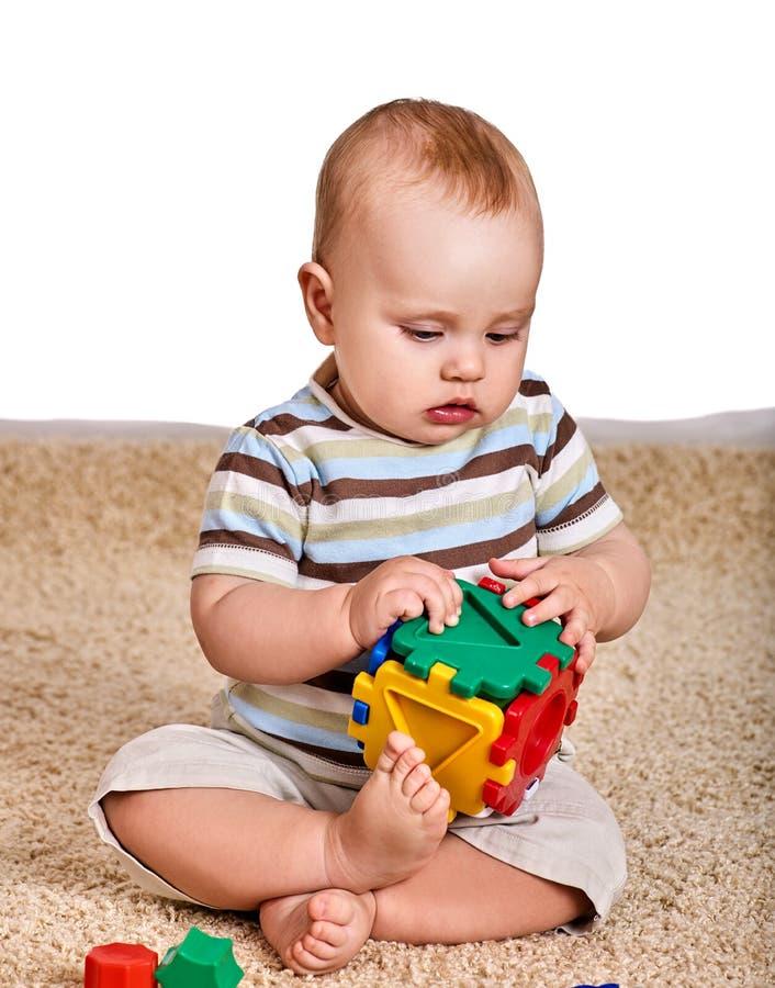 Dziecko chłopiec kursowanie z łamigłówki zabawką na podłoga obrazy stock