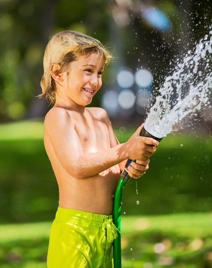 Dziecko, chłopiec lub dzieciak, bawić się z wodnym wężem elastycznym outdoors obraz royalty free
