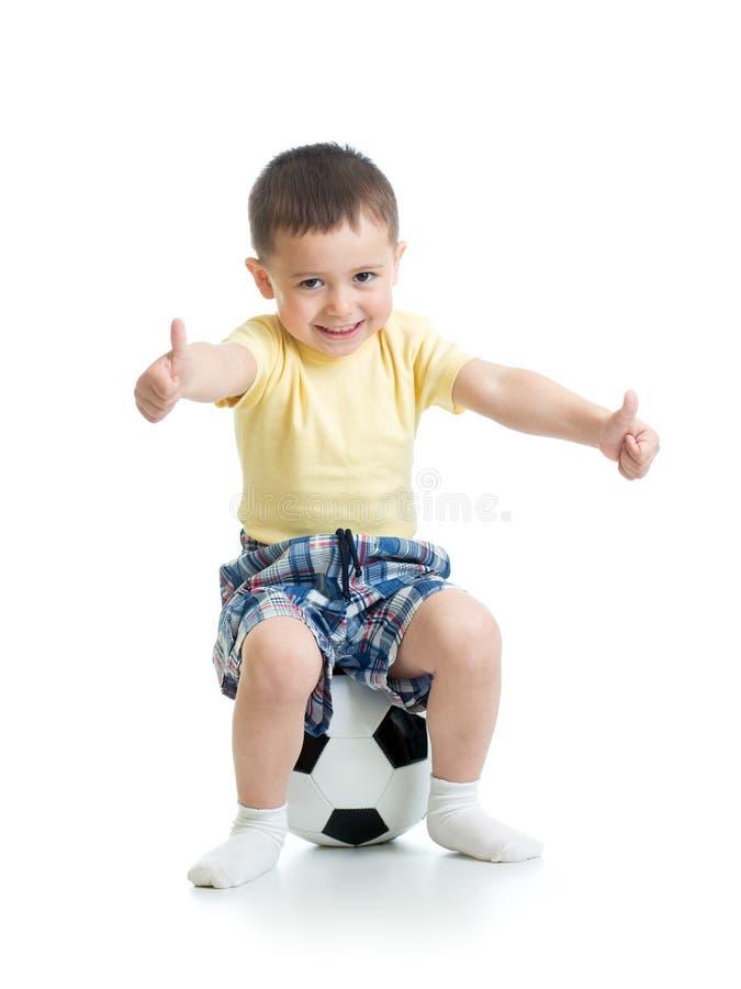 Dziecko chłopiec obsiadanie na piłki nożnej piłce z aprobatami podpisuje fotografia royalty free