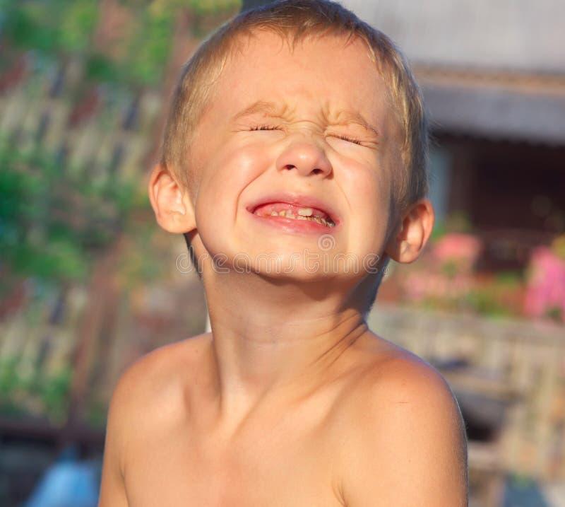 Dziecko chłopiec robi bolesnemu płaczowi Stawia czoło pokazywać łydka zębów gnicie obrazy stock