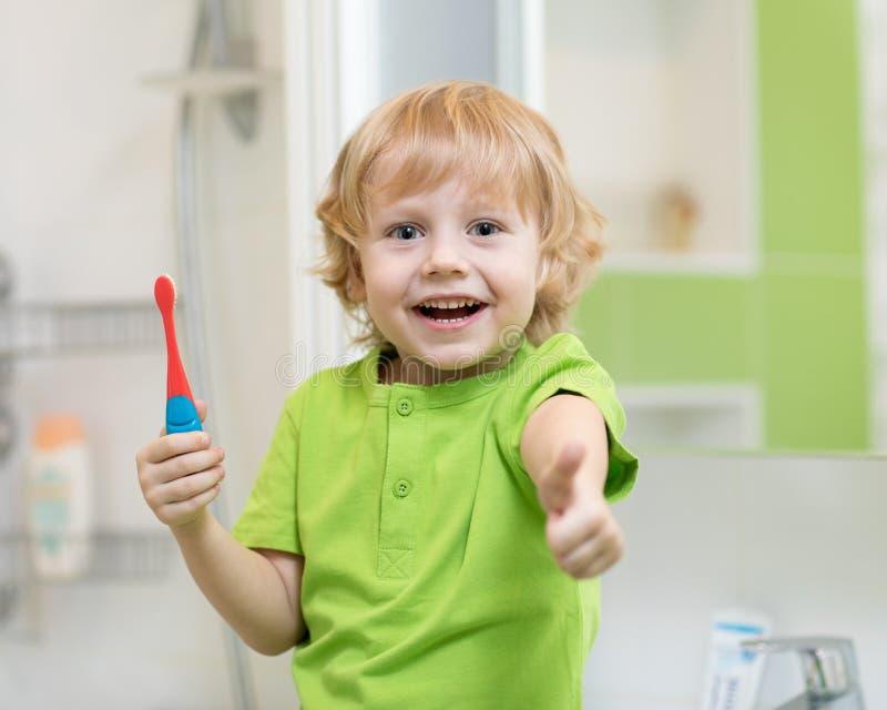 Dziecko chłopiec szczotkuje zęby w kąpielowych i pokazują aprobatach zdjęcia royalty free