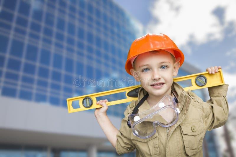 Dziecko chłopiec Ubierał Up jako złota rączka przed budynkiem obraz stock