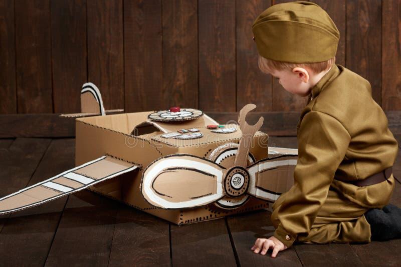 Dziecko chłopiec ubiera, ciemny drewniany tło, zmiękcza gdy żołnierz w retro wojskowych uniformach naprawia samolot robić karton obrazy royalty free