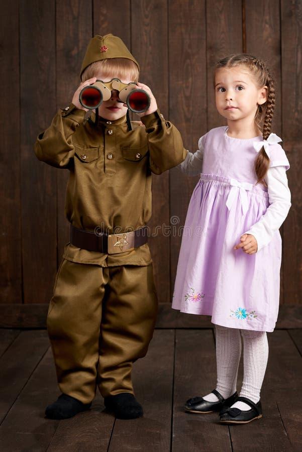 Dziecko chłopiec ubiera gdy żołnierz w retro wojskowych uniformach i dziewczyna w menchiach ubieramy obrazy royalty free