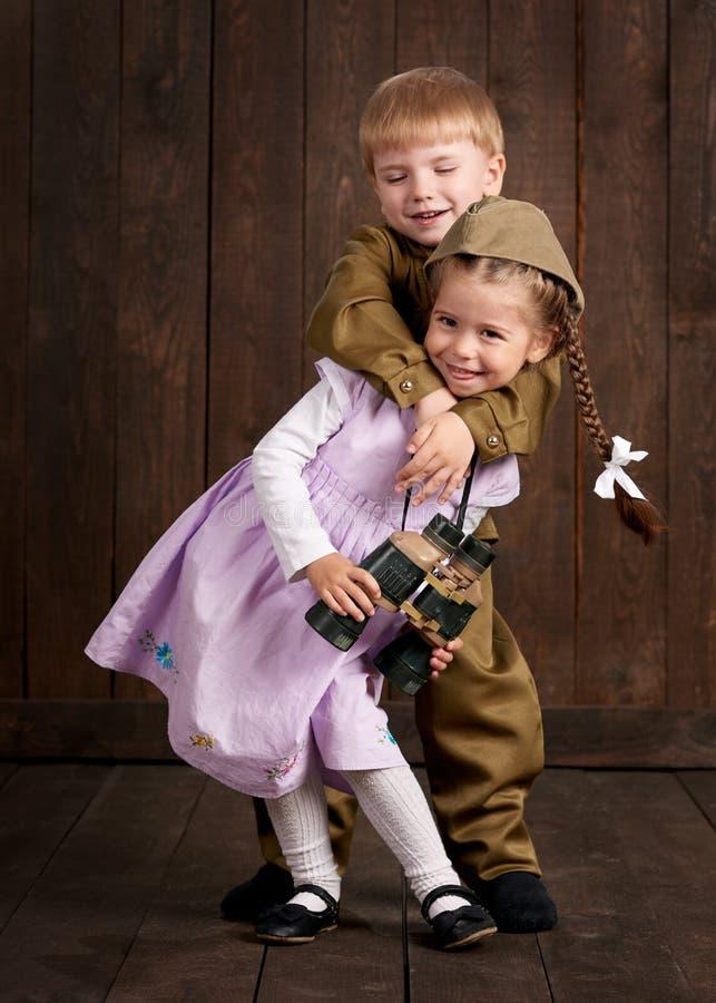Dziecko chłopiec ubiera gdy żołnierz w retro wojskowych uniformach i dziewczyna w menchiach ubieramy zdjęcia stock
