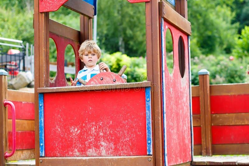 Dziecko chłopiec udaje jechać imaginacyjnego samochód na dzieciaka boisku fotografia stock