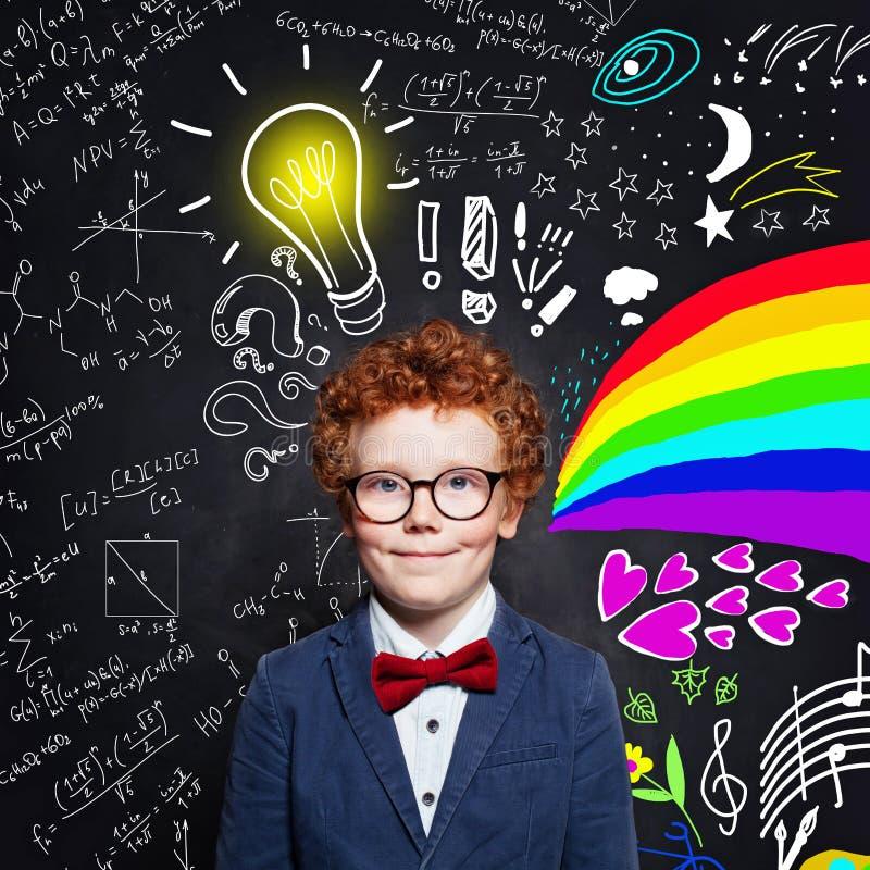 Dziecko chłopiec z imbirowymi włosianymi jest ubranym szkłami na blackboard tle z nauk formułami, sztuka wzorem i żarówka pomysłu zdjęcie royalty free
