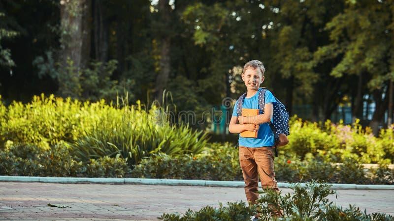 Dziecko chodzi do szkoły podstawowej portret szczęśliwego dziecka z teczką na plecach zdjęcia stock