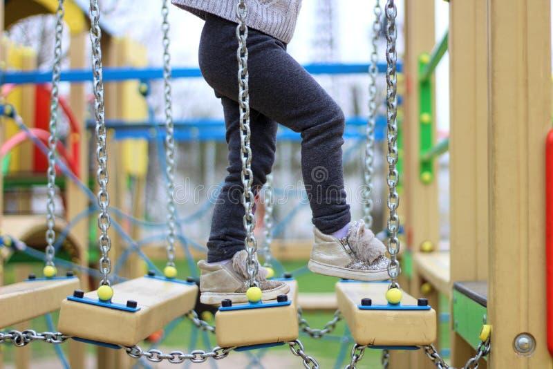 dziecko chodzi na zawieszonym children& x27; s łańcuchu droga na boisku zdjęcia royalty free