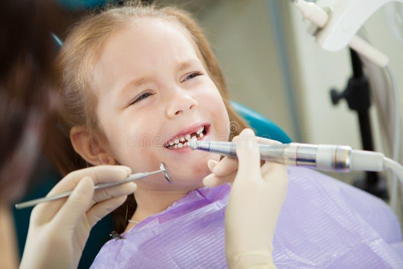Dziecko czuje toothache podczas polerowniczej procedury w dentysty krześle obraz stock