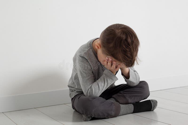 Dziecko czyj depresja siedzi na pod?odze zdjęcie stock