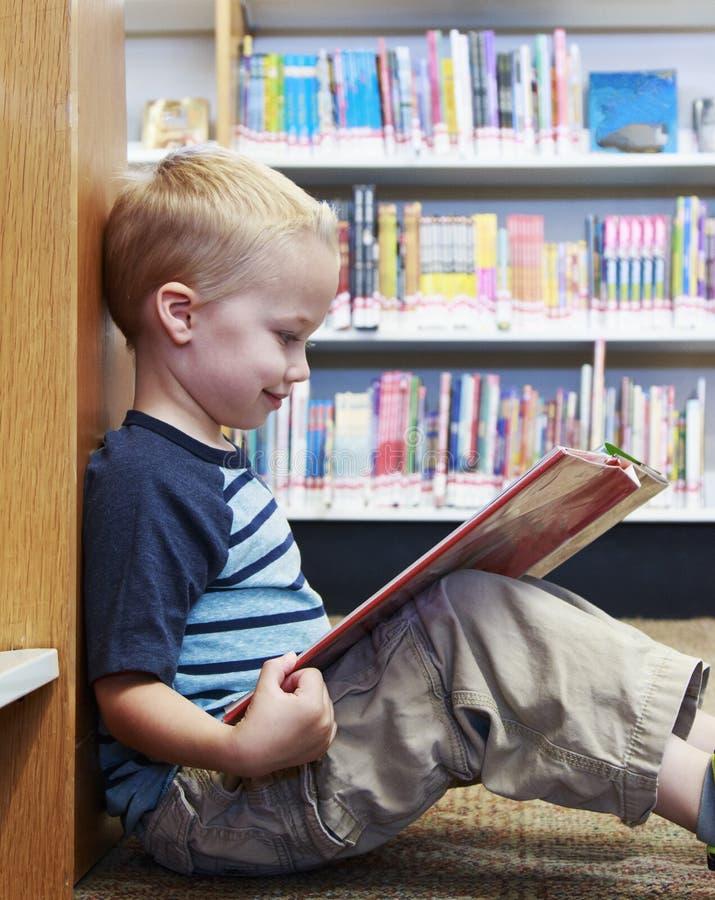 Dziecko czyta książkę przy biblioteką fotografia royalty free