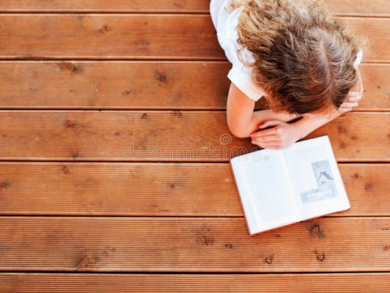 Dziecko czytelnicza książka przy drewnianą podłoga obrazy stock