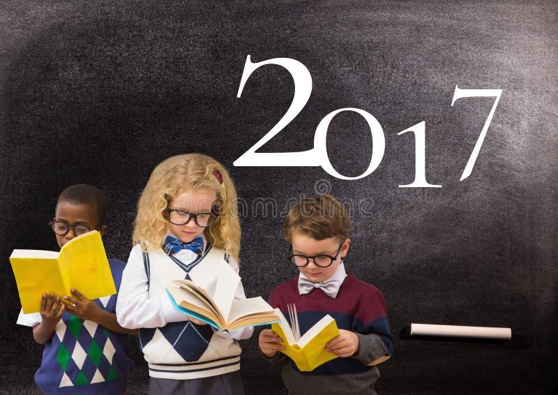 Dziecko czytelnicze książki przeciw blackboard z 2017 nowy rok znakiem zdjęcie royalty free