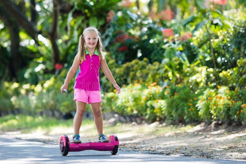 Dziecko dalej unosi się deskę Dzieciak przejażdżki hulajnoga obrazy royalty free