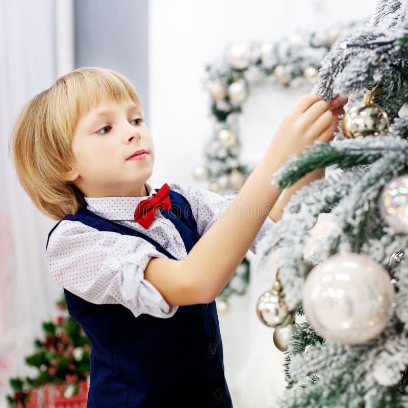 Dziecko dekoruje choinki w pokoju Pojęcie zima zdjęcie stock