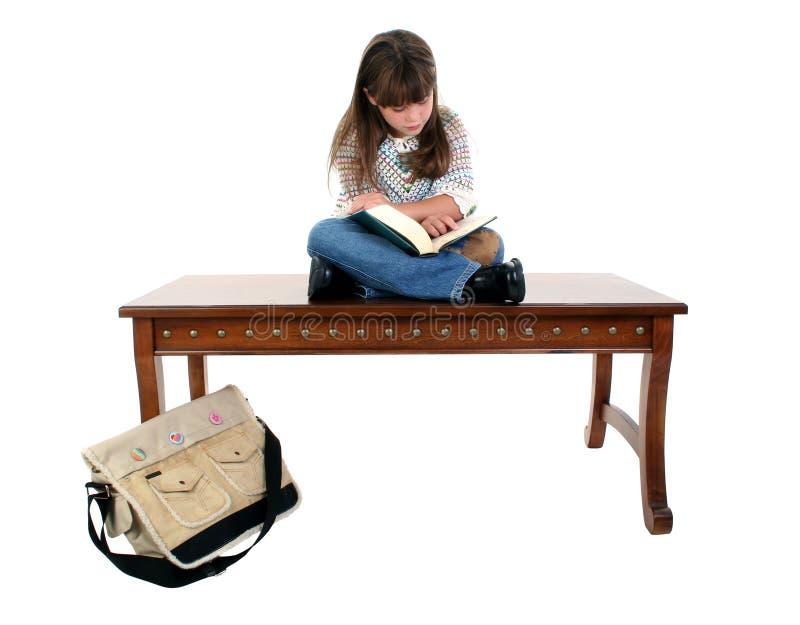 dziecko do czytania książki posiedzenia tabeli obrazy stock