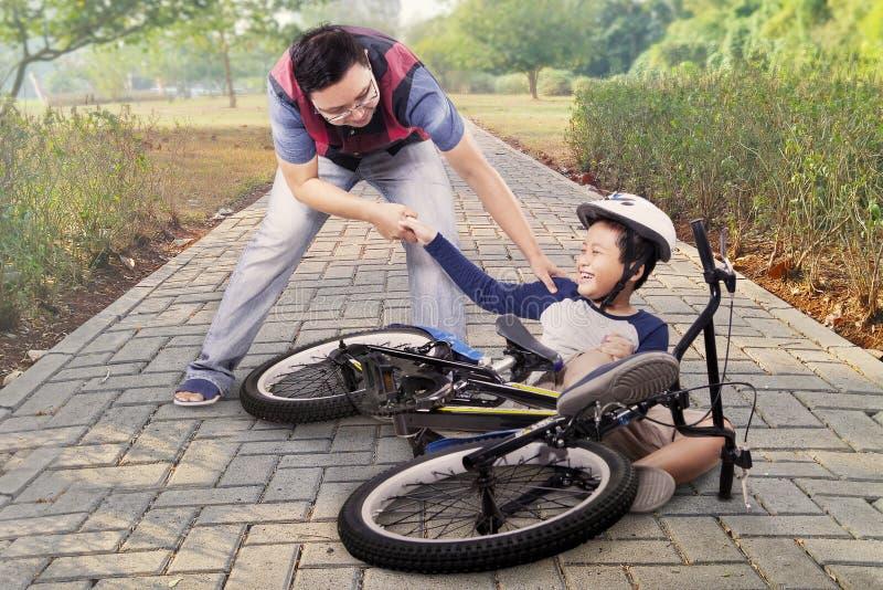 Dziecko dostaje trzaska i pomagać tata obraz royalty free